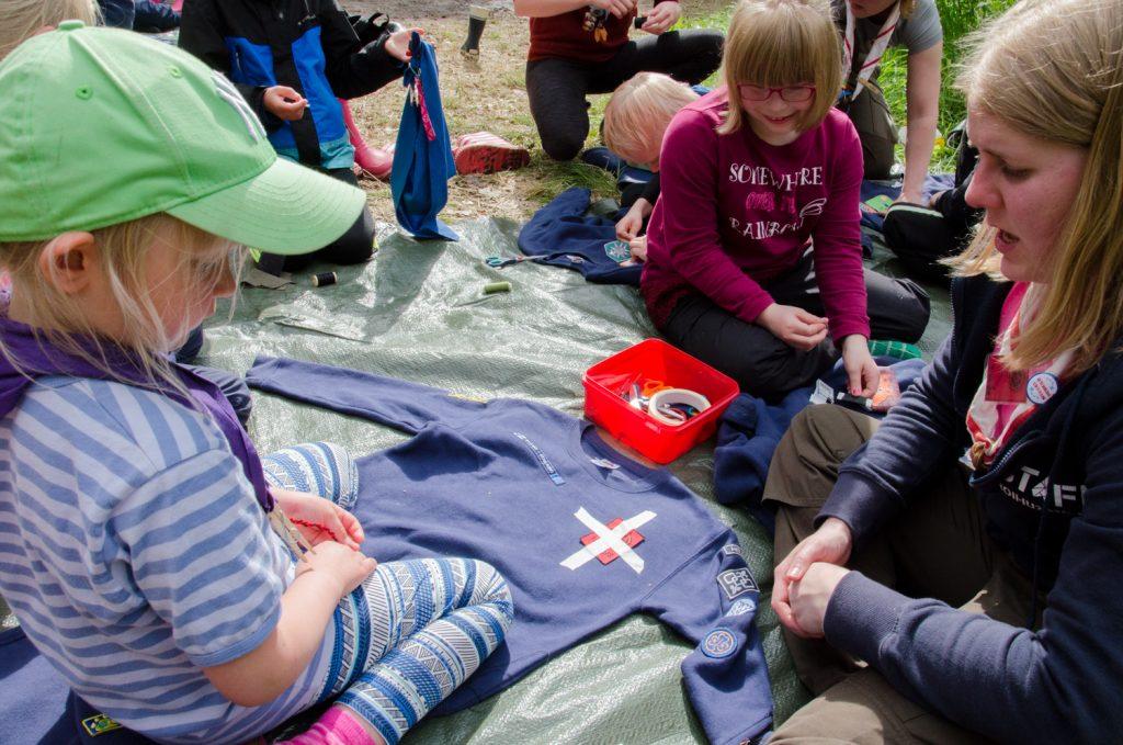 Sudenpennut ompelemassa leirimerkkejä